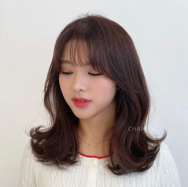 Kiểu tóc uốn đuôi tóc nhẹ kết hợp mái thưa giúp nổi bật và che bớt các khuyết điểm